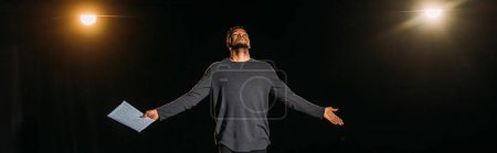 Photo pour Photo panoramique d'un acteur africain américain tenant un scénario et se tenant debout sur scène pendant la répétition - image libre de droit