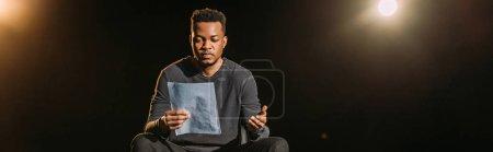 Photo pour Plan panoramique de l'acteur afro-américain tenant le scénario sur scène pendant la répétition - image libre de droit