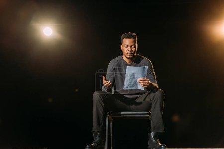 Photo pour Beau comédien afro-américain tenant le scénario sur scène pendant la répétition - image libre de droit