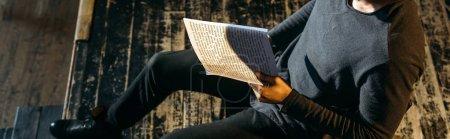 Photo pour Plan panoramique de l'acteur afro-américain lisant le scénario sur scène pendant la répétition - image libre de droit