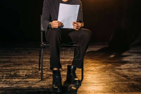 Photo pour Vue recadrée de l'acteur afro-américain tenant le scénario sur scène pendant la répétition - image libre de droit