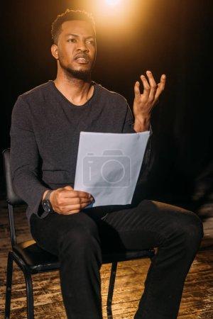 Photo pour Beau comédien africain américain tenant le scénario sur scène pendant la répétition - image libre de droit