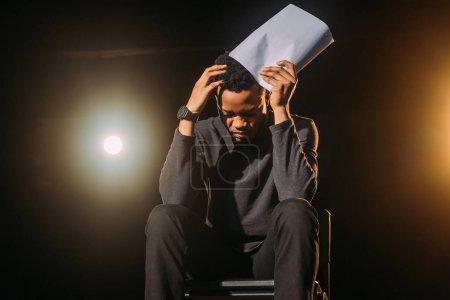 Photo pour Acteur afro-américain stressé tenant scénario sur scène pendant la répétition - image libre de droit