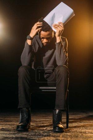 Photo pour Acteur afro-américain émotionnel tenant scénario sur scène pendant la répétition - image libre de droit