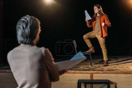 Photo pour Foyer sélectif de beau jeune acteur sur le casting avec metteur en scène de théâtre - image libre de droit