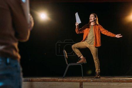 Photo pour Beau jeune acteur avec scénario répétition avec metteur en scène - image libre de droit