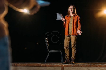 Photo pour Jeune acteur avec scénario sur casting avec le metteur en scène - image libre de droit