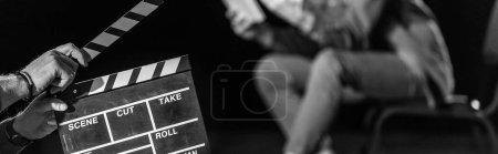 Photo pour Plan panoramique de l'acteur avec clin d'oeil devant, isolé sur noir, noir et blanc - image libre de droit