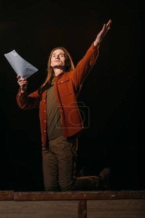 guapo actor con guion jugando en el escenario durante el ensayo