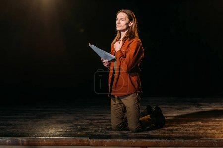 Photo pour Beau comédien avec scénario jouant sur scène pendant la répétition au théâtre - image libre de droit