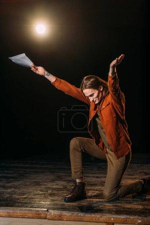 Photo pour Beau acteur avec scénario jouant sur scène pendant la répétition - image libre de droit