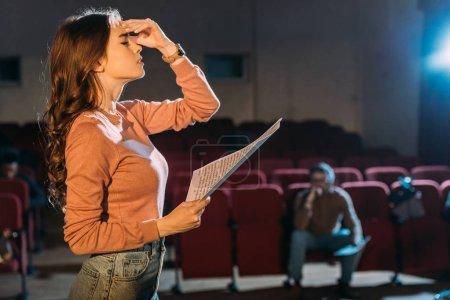 Photo pour Mise au point sélective du metteur en scène de théâtre et actrice attrayante avec scénario sur scène - image libre de droit