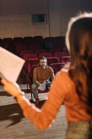 Photo pour Focalisation sélective du metteur en scène et de l'actrice avec scénario dans le théâtre - image libre de droit