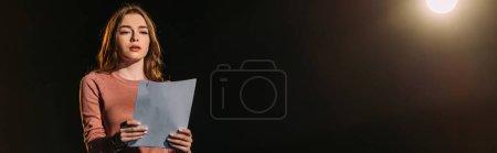 Photo pour Plan panoramique de jeune actrice attrayante scénario de lecture sur noir - image libre de droit