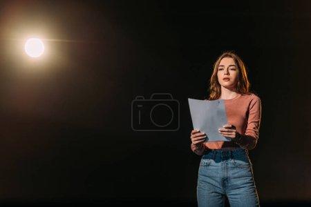 Photo pour Belle jeune actrice lecture scénario sur noir - image libre de droit