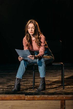 Photo pour Belle jeune actrice lecture scénario sur scène dans le théâtre - image libre de droit