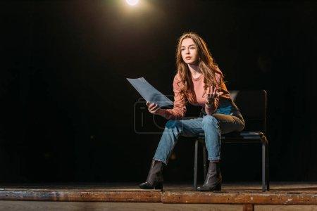 Photo pour Jeune actrice séduisante avec scénario jouant un rôle sur scène dans le théâtre - image libre de droit