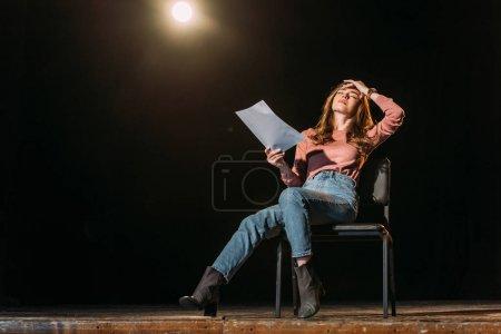 Photo pour Attrayant jeune actrice jouant le rôle avec scénario sur scène dans le théâtre - image libre de droit