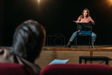 Photo pour Mise au point sélective du metteur en scène et de l'actrice jouant un rôle avec scénario dans le théâtre - image libre de droit