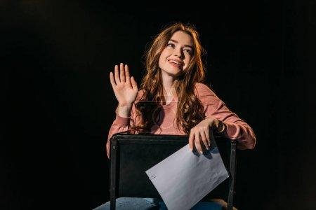 Photo pour Joyeuse jeune actrice avec scénario assis sur une chaise sur scène dans le théâtre - image libre de droit