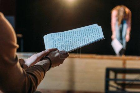 Photo pour Focalisation sélective du metteur en scène avec scénario applaudissant à l'actrice s'inclinant sur scène - image libre de droit