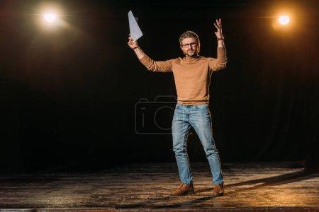 Photo pour Metteur en scène de théâtre émotionnel tenant scénario et debout sur scène pendant la répétition - image libre de droit