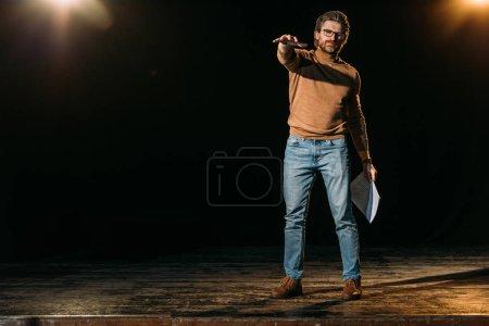 Photo pour Metteur en scène émotionnelle tenant scénario et debout sur scène pendant la répétition dans le théâtre - image libre de droit