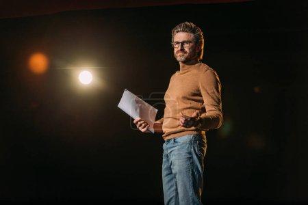 Photo pour Acteur mature tenant scénario et debout sur scène pendant la répétition dans le théâtre - image libre de droit
