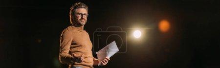 Photo pour Photo panoramique d'un acteur mûr tenant un scénario et se tenant debout sur scène pendant la répétition au théâtre - image libre de droit