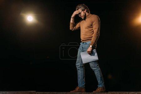 Photo pour Scénario de tenue d'acteur mature stressé et debout sur scène pendant la répétition - image libre de droit