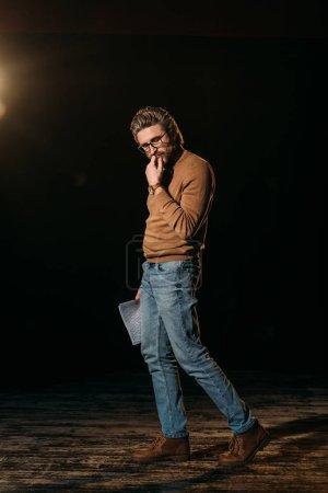 Photo pour Acteur mature réfléchi tenant scénario et debout sur scène pendant la répétition - image libre de droit