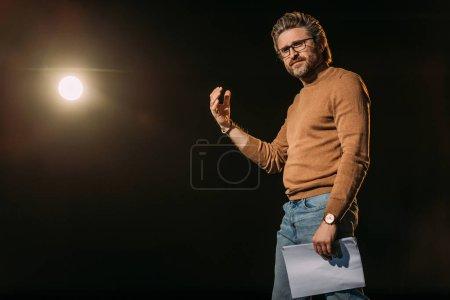 Photo pour Beau acteur mature tenant le scénario et debout sur scène pendant la répétition - image libre de droit