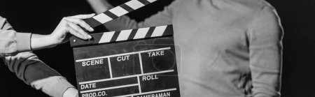 Photo pour Plan panoramique de l'acteur avec panneau à clins devant, isolé sur noir, noir et blanc - image libre de droit