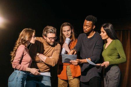 Photo pour Acteurs et actrices multiethniques lisant le scénario sur scène dans le théâtre - image libre de droit