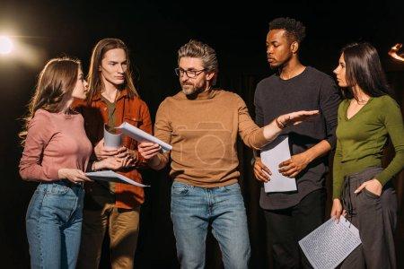 Photo pour Acteurs et actrices multiethniques répétant avec le metteur en scène du théâtre sur scène - image libre de droit