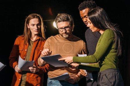 Photo pour Metteur en scène, acteurs multiculturels et actrice répétant avec des scénarios sur scène - image libre de droit
