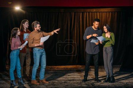 Photo pour Jeunes acteurs et actrices multiethniques répétant avec un metteur en scène mature sur scène - image libre de droit