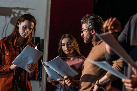 Photo pour Metteur en scène, acteur et actrice répétant avec des scénarios sur scène - image libre de droit