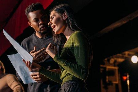 Photo pour Acteur et actrice multiethnique ayant répété sur scène dans un théâtre - image libre de droit