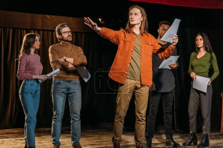 Photo pour Acteurs et actrices multiculturelles répétant avec des scénarios sur scène dans le théâtre - image libre de droit