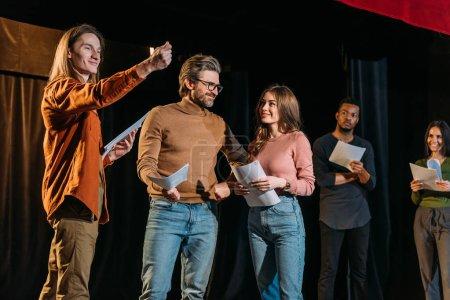 Photo pour Acteurs et actrices multiculturelles répétant sur scène dans le théâtre - image libre de droit