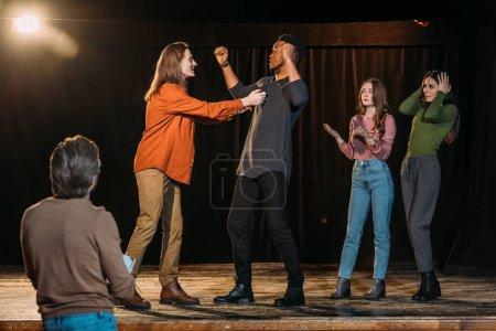 Photo pour Acteurs multiethniques répétant la lutte sur scène dans le théâtre - image libre de droit