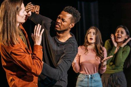 Photo pour Actrices effrayées et combattre les acteurs multiculturels jouant dans le théâtre - image libre de droit
