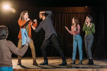 Photo pour Acteurs multiculturels répétant combat sur scène dans le théâtre - image libre de droit