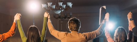 Photo pour Plan panoramique d'acteurs et d'actrices les mains en l'air et éclairage dramatique - image libre de droit