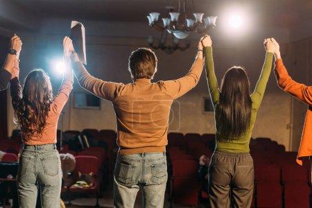 Photo pour Vue de dos des acteurs et actrices avec les mains en l'air sur la répétition - image libre de droit