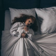 Top view of paranormal gothic girl in nightgown ly...