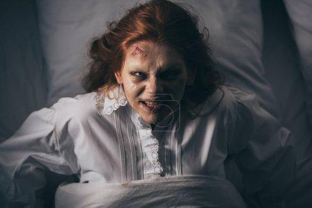 Photo pour Vue du dessus de la fille paranormale en chemise de nuit couchée dans le lit - image libre de droit
