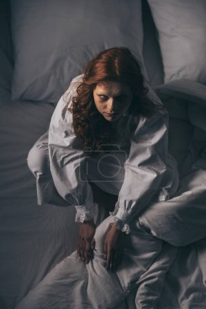 Photo for Overhead view of demoniacal scary woman in nightgown sitting in bed - Royalty Free Image