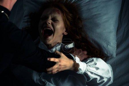 Photo pour Exorciste tenant hurler fille obsédée dans le lit - image libre de droit